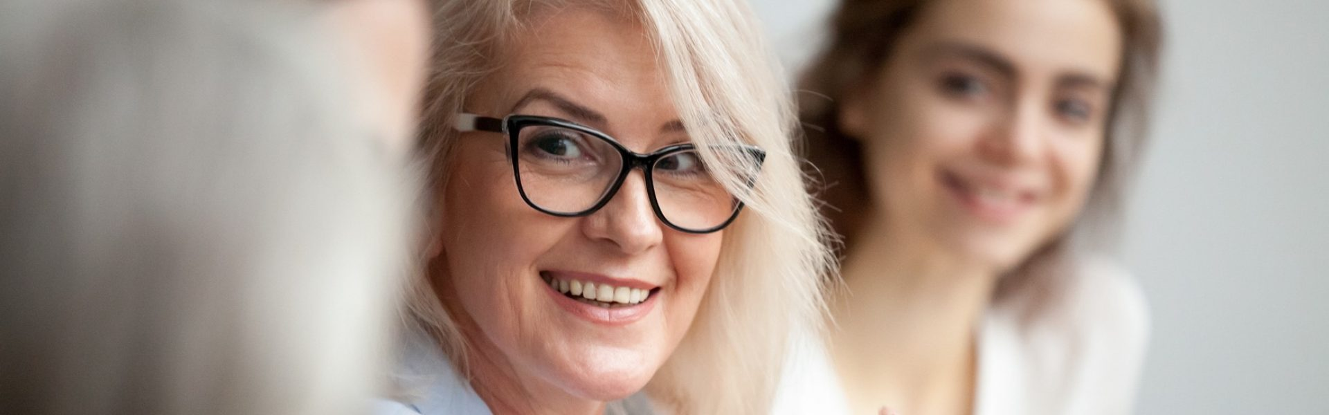 Horizontal close up photo focus aged attractive businesswoman boss in glasses listen colleague ideas information at briefing meeting negotiation with business partners banner for website header design (Horizontal close up photo focus aged attractive b